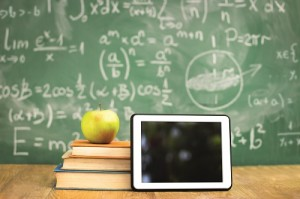 Digital tablet and apple on stack of books